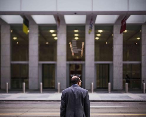 Un homme de dos et face à un bâtiment, prêt au changement.