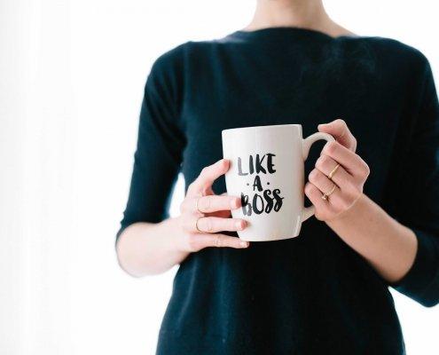 """Une femme au t-shirt noir tenant une tasse de café sur laquelle est écrit """"like a boss""""."""