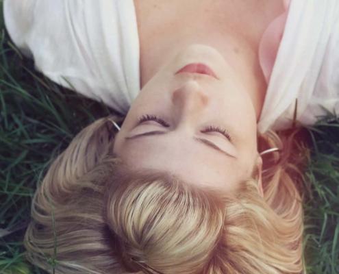 Une femme au visage apaisé allongée dans l'herbe