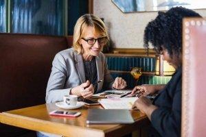 Deux femmes d'entreprise en train de travailler autour d'un café.